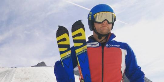 Man on a snowy mountain holding skiis