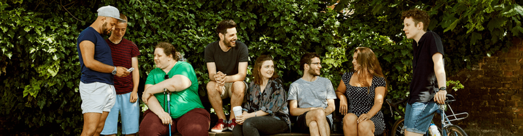Group of people sitting together on a park bench