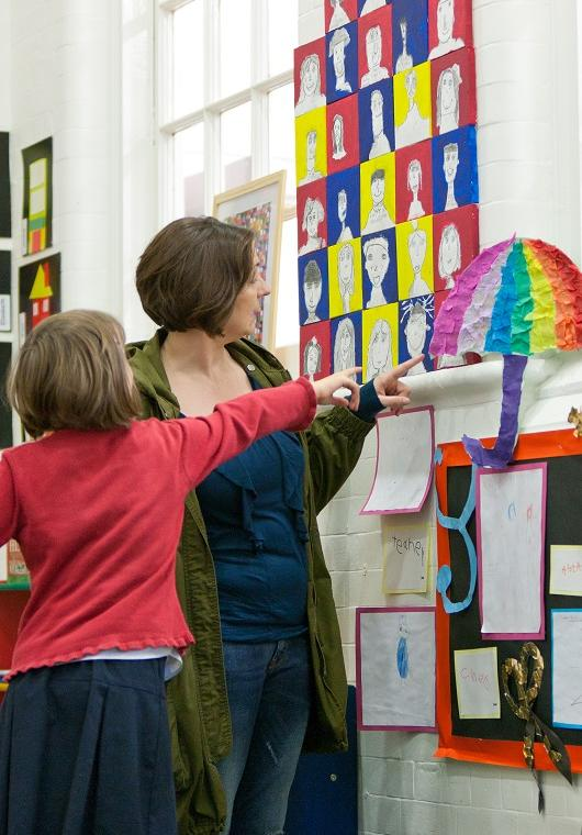 Child in the classroom with adult looking at wall display