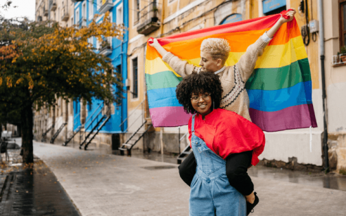 A Black young person has a white young person on their shoulders - the latter holds up a Pride flag. They are on a street in daylight. One of the buildings behind them is bright blue, the others are a muted yellow.