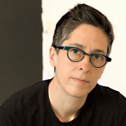 White person in black t-shirt and black glasses sits cross-legged against a black and white wall and looks at the camera