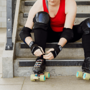 White person in a red top and black leggings sits on steps and ties on rollerskates with rainbow laces