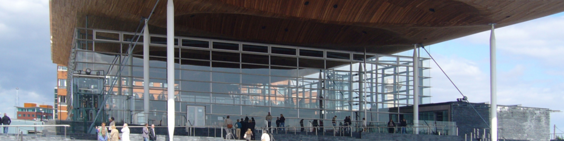 People walk up the steps to the Senedd on a clear blue day.